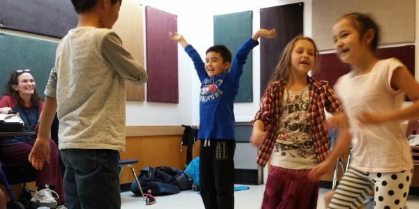 Children laugh and play in an artsREACH theatre workshop.